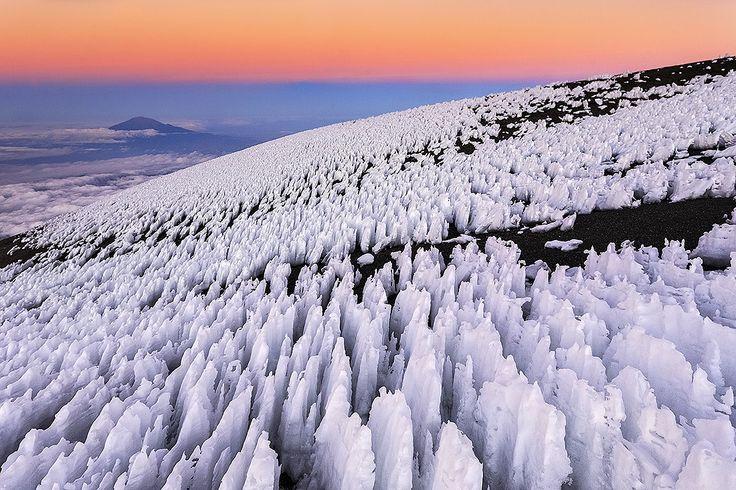 500px 上の Bene Santos の写真 Penitents in Kilimanjaro アフリカのキリマンジャロ山の山頂付近で撮影された多数の氷の柱の写真。bit.ly/1zMC5r3  「ペニテンテス」と呼ばれる現象で、ひざまずいて懺悔する人を示す言葉が語源。残雪や氷河の中で側面よりも頂部が融けにくい気象条件が揃うと発現する。背後の空の色も美しい。