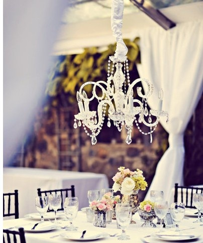 A Small Chandelier Over Every Round Table Helps To Light Up The Whole Room