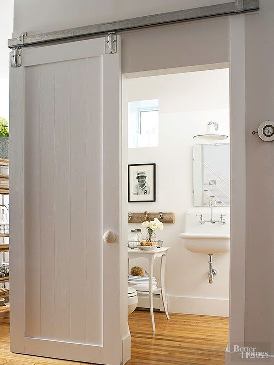 This country-style bathroom knows how to make a statement with its jaw-dropping sliding barn door on a wall-mount track. The door takes on cottage character to match the bathroom's timeworn furnishings and fixtures.