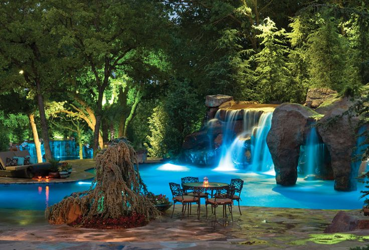 With landscape lighting and a colorfully lit pool, this backyard is an enchanting dreamland, featuring multiple rock waterfalls and a secret entry to the grotto. Caviness Landscape Design, Edmond, Oklahoma. Photography by K.O. Rinearson http://www.luxurypools.com/builders-designers/caviness-landscape-design.aspx