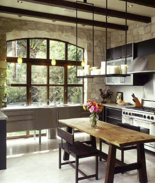 """As seen in Urban Country style - """"Beams, stone walls, and rustic table are classic country elements in this sophisticated California kitchen by DuCharme Architecture, which features three layers of lighting (central candle-like chandelier, the recessed lighting, and the pendants over the sink). The urban materials - steel, polished granite, and glass - are highlighted by the soft gray 'floating' cabinetry against the window, and a wonderful old wooden table.""""  www.amazon.com"""