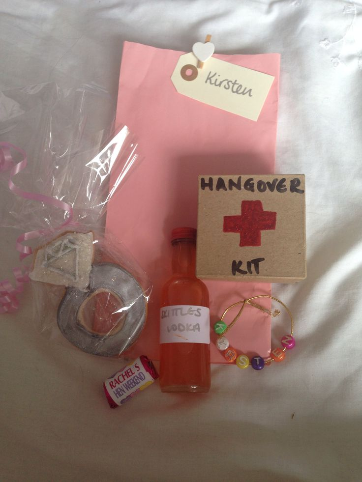 Homemade Hen Bachelorette party bags containing skittles vodka, bead name bracelet, Hangover Kit (with tea bag, painkillers, mints and chocolate inside), personalised Sweethearts, and homemade diamond ring biscuits