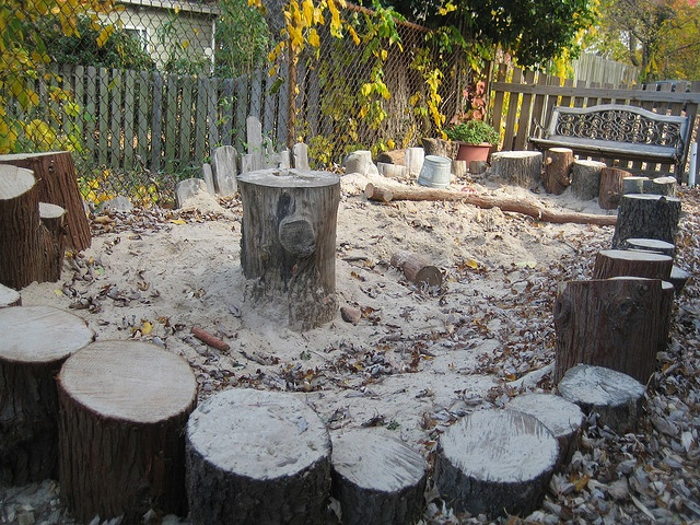 Placing logs for stools around sandbox, children can know more about nature.