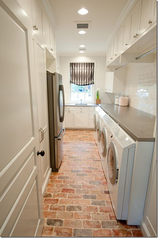 Laundry room with brick floors, white subway tile, solid surface counter, hanging rods for clothes