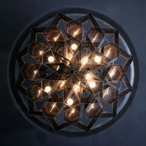 MANDALA NO.2 - BLACK DIAMOND A massive intense Illuminated Mandala sculpture inspired by Islamic patterns which have been translated into three dimensions through the extrusion of the complex interlocking geometry. Made from lasercut stainless steel frames, chrome plated or lacqured solid brass components, ballchain in several optional finishes. Illuminated by a combination of surface mounted and suspended G4 Halogen lamps.