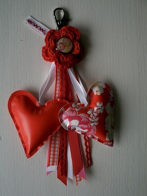 Tashanger in rood oranje tinten.     Met twee hartjes van tafelzeil, gehaakte bloem en veel linten.