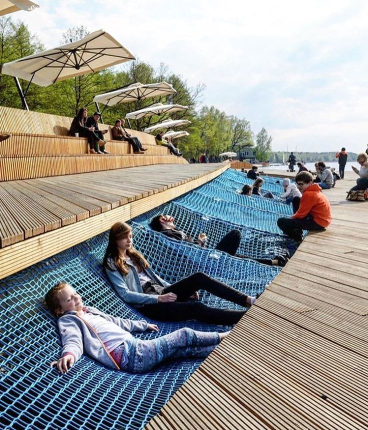 netting for relaxing interrupts the wooden boardwalk of this public project by RS+ architects in poland allowing residents to lie, sit and socialise while facing the lake.  #designboom #architecture
