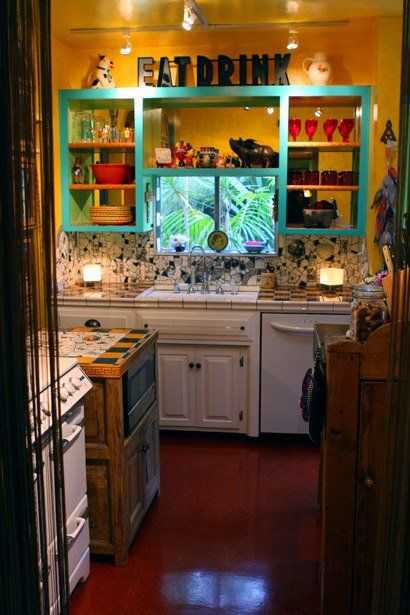 """""""Artists piece together a colorful look with mosaics in their L.A. bungalow. Beserra-Byrd home in Silver Lake. The couple's lemon-orange kitchen, dominated by a 1949 O'Keefe & Merritt stove, completes that surge."""" Teal shelves. Yellow walls. EAT DRINK sign. Kitchen storage"""