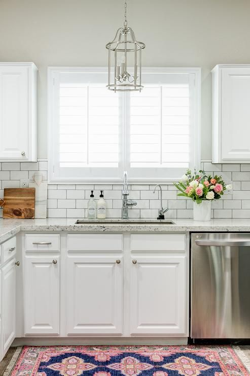 chic white kitchen features white cabinets paired with white granite countertops and a white subway tile