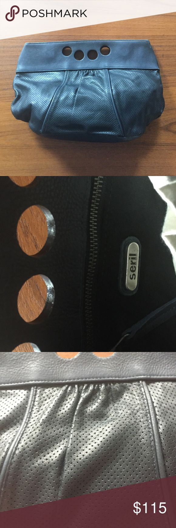 Seril navy clutch (As seen on Angelina Jolie!) Really cool finger-hole bag-- kind of like a bowling ball? Perforated navy leather on bottom and regular pebbled texture on top. See it on Angelina for size/scale! Will come with a dust bag. Seril Bags Clutches & Wristlets