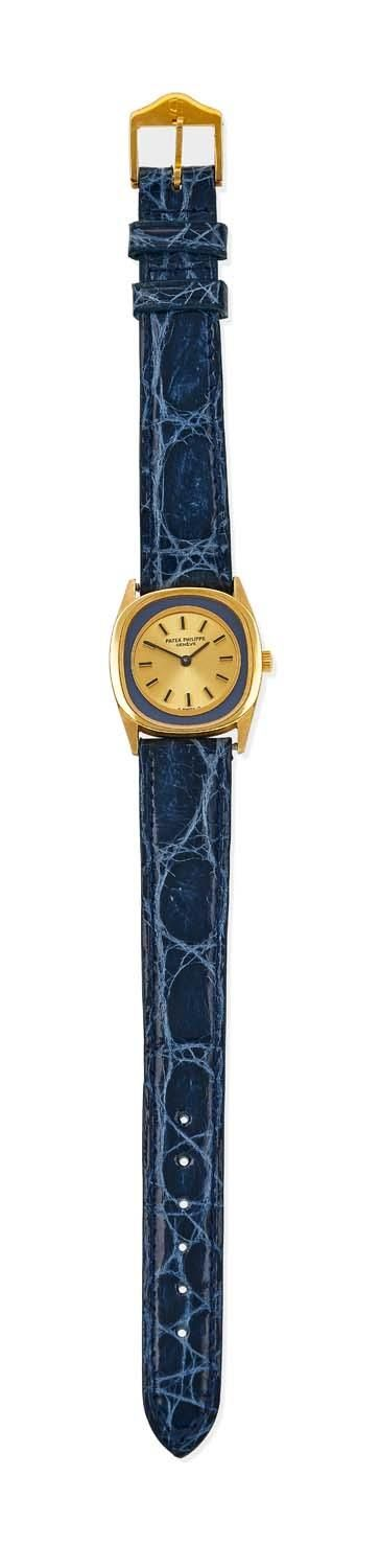 A Lady's gold Lady Ellipse wristwatch, Patek Philippe, circa 1974. Manual. 24mm. Ref: 4172. Cal. 16-250. Serial number 1272224. Oval case with blue outer band and circular gold dial with applied black baton numerals. 18ct yellow gold case, dial, crown and movement signed. Non- original blue leather strap. Extract from the Archives, dated June 15, 2015. - Price Estimate: $6500 - $7500
