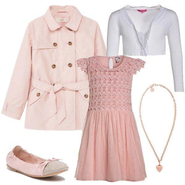 Il vestito elegante ha il corpino e le maniche in pizzo, mentre la gonna è in tulle leggero. Il cardigan corto è chiuso con un laccetto e la collana color oro rosa con il cuoricino rende il look ancora più romantico. Sopra, il trench doppiopetto. Ai piedi, le comode ballerine rosa e oro con il fiocchetto.