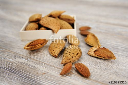 Almonds and almond nuts on a rustic wood background