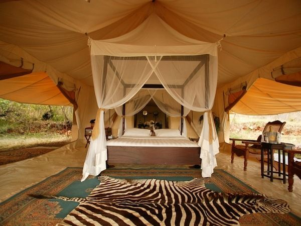 Cottar's Camp, luxurious master bedroom with large king bed and white expansive canopy with wood paneled floors Kenya, Africa safaris