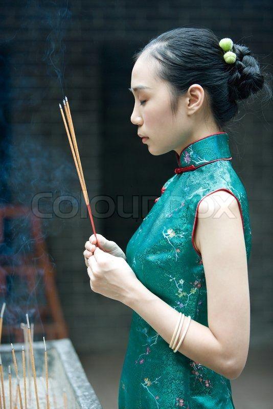 Stock Bild von 'Junge Frau trägt traditionelle chinesische Kleidung, hält Weihrauch, Seitenansicht'