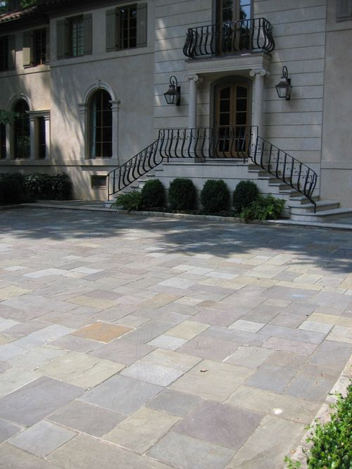 Formal Blue stone motor court in a Random Ashlar pattern with Granite cobble curbing and front entrance to the estate home in the background