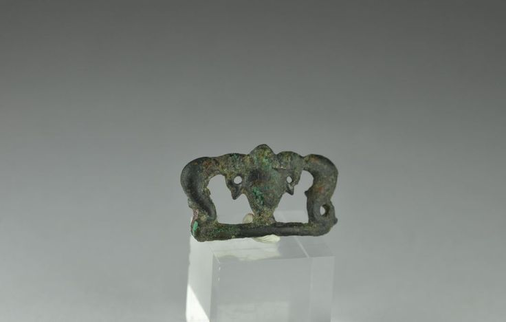 Roman brooch, roman bronze brooch in shape of two dolphins and vase in center, 1st-3d century A.D. . Private collection