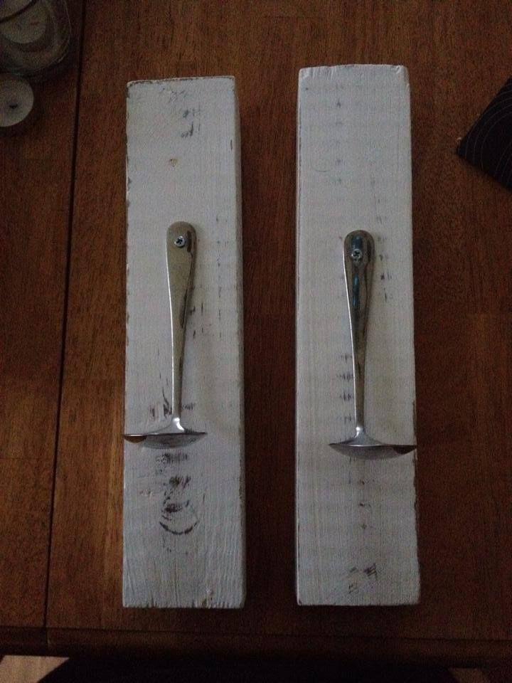 Två vita ljuslampetter med skedar till att sätta värmeljus på.