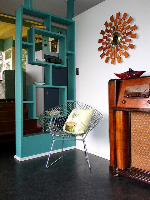No lugar de uma parede simples, você pode dividir ambientes com móveis bem desenhados. Na foto, vemos que com a cadeira Bertoia e os móveis retrô, foi criado um pequeno espaço para relaxar em casa.