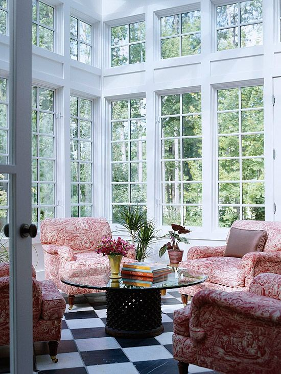 Stand-Out Sunroom - Tall, transom-topped windows stretch up the walls, allowing an abundance of natural light to filter inside this elegant farmhouse-style sunroom. A classic black-and-white checkerboard pattern painted onto the floor adds flair underfoot. Four comfy chairs covered with red toile fabric create a cozy, stylish sitting area.
