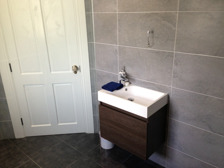 Ensuite, walnut basin looks good with grey tiles. Tap at end good design for small basin.