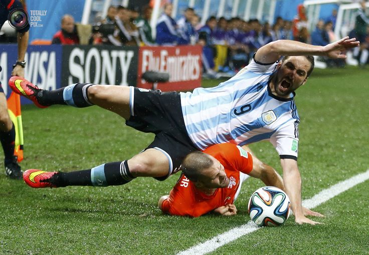 World Cup 2014: The Netherlands vs Argentina Semi-Final Highlights - Argentina's Higuain falls on Vlaar of the Netherlands during their 2014 World Cup semi-finals at the Corinthians arena in Sao Paulo. DOMINIC EBENBICHLER/REUTERS