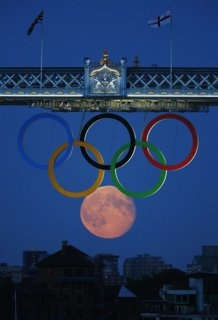 Pretty!! -- The full moon rises through the Olympic Rings hanging beneath Tower Bridge during the London 2012 Olympic Games
