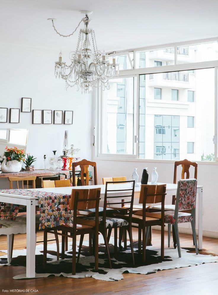 Sala de jantar com mesa de madeira, cadeiras diferentes e tapete de pele de vaca.