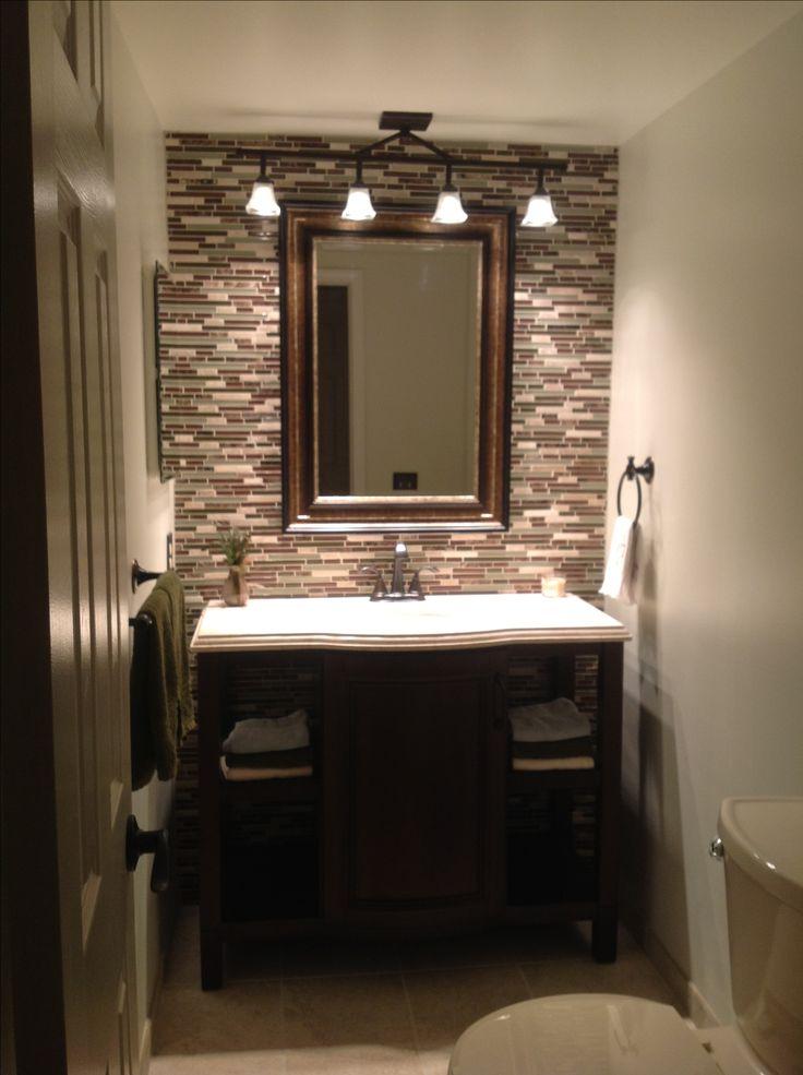 Dark cabinet, light counter, tile, lighting, mirror.