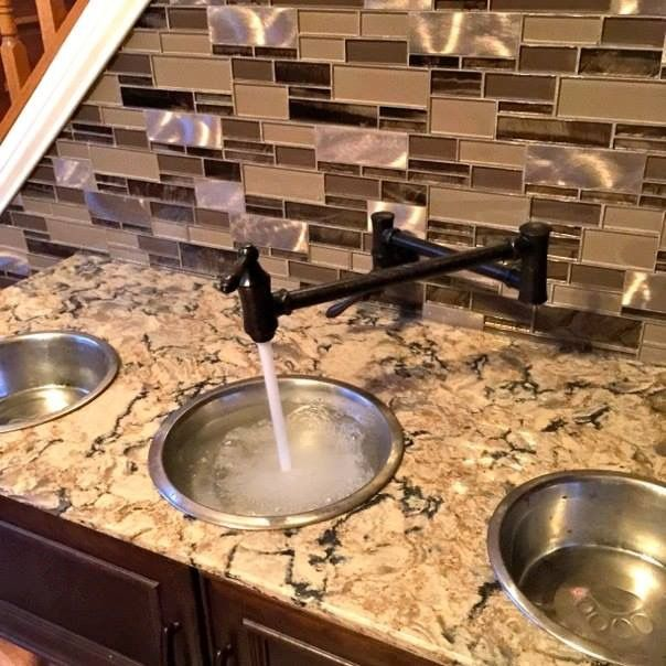 """This home has """"doggone"""" good design! This design, by Kendra Roenker of Modern Builders Supply, makes pet care easy for the owners, and luxurious for the dogs. The amenities go way beyond the basics. The faucet is placed above the water bowls—no more toting water from the kitchen sink and leaving a wet trail behind. The beds aren't just beds—they are raised beds with stepping stools. The feeding station holds toys, food, leashes and dog grooming tools."""