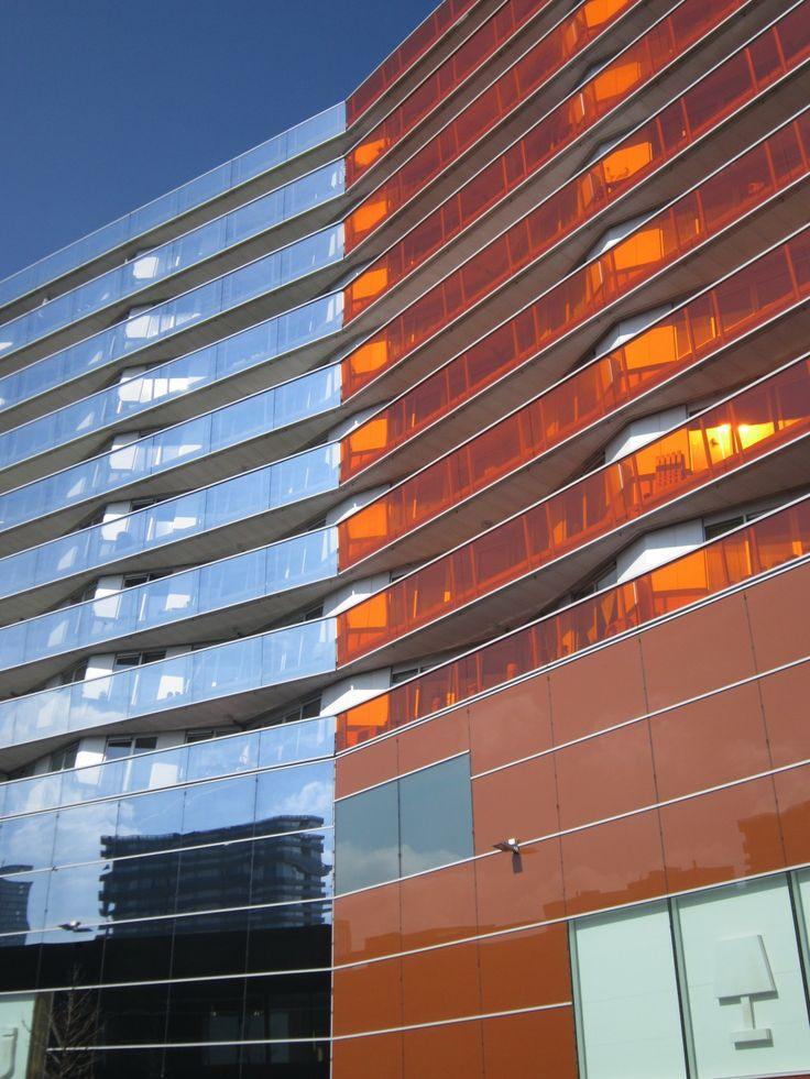 Deze glazen verdiepingsbalustrades zijn in dit gebouw in de knik gesplitst. Dit is gedaan in de kleuren cyaan en oranje deze zijn complementair aan elkaar en versterken daarom elkaars stralingskracht.