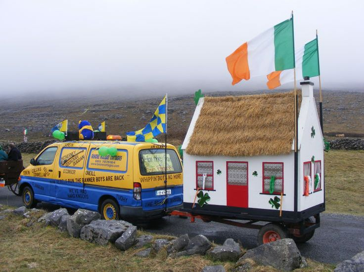 An Irish thatched cottage being towed by a van painted in the colors of the County Clare hurling team