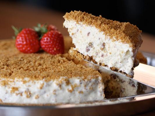 Osteiskake med sjokolade - Smakfull iskake med sjokoladebiter og porøs kjeksbunn. Like populær hos barna som hos de eldre. Lettvint kake som kan være kjekk å ha på lur hvis en får uventet besøk.