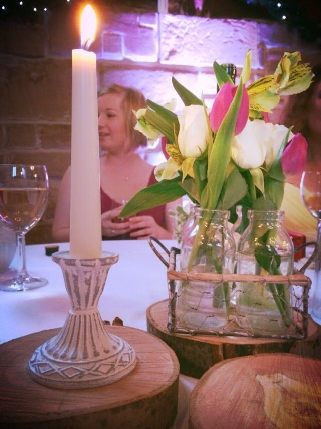 Centre pieces - old candle sticks and jars of flowers stacked on antique books and slices of eucalyptus wood. Homemade, with each table having an individual centrepiece using similar materials, this is an example one of 10!