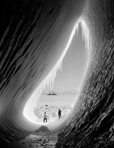 Geologist Thomas Griffith Taylor (1880 - 1963) and meteorologist Charles Wright (1887 - 1975) in the entrance to an ice grotto during Captain Robert Falcon Scotts Terra Nova Expedition to the Antarctic, 5th January 1911. The Terra Nova is in the background. Photo: Scott Polar Research Institute, , H.G. Pointing/Terra Nova / 2009 Getty Images