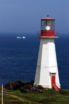 Iceberg and Quirpon Lighthouse An iceberg, one of many carried down from Greenland on the Labrador Current, floats past Quirpon Lighthouse on Newfoundland. Photo by Peter Potterfield.