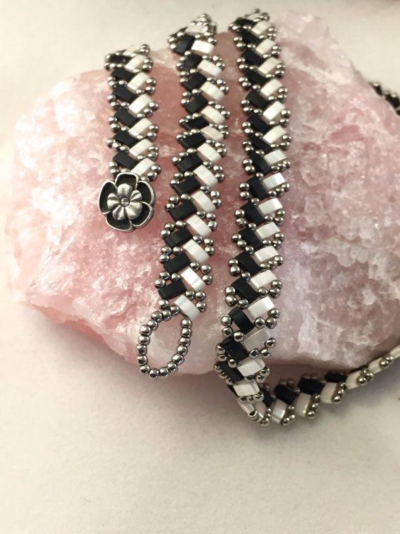 Dies ist ein neues nehmen auf dem Wrap-Armband - komplett-Perlen - und es kann als Halskette getragen werden!!! Es gleitet auf der Haut wie Seide. So komfortabel.  Die japanische halbe Tila-Perlen sind in zwei Farbtönen, Matt schwarz und Perlmuttweiß - hell und dunkel. Sie haben ein sehr Yin Yang aussehen. Die halbe Tila-Perlen werden zusammen mit Gunmetal Preciosa Rocailles, eine traditionelle tschechische Glasperle Saatgut gewebt. Das Armband ist 3/8 breit und 21 lang. Es ist mit einem…