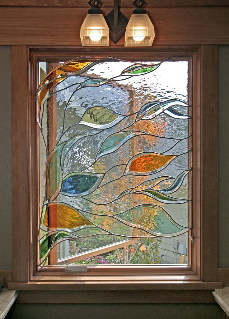 Stained glass window in bathroom depicting blowing branches and leaves
