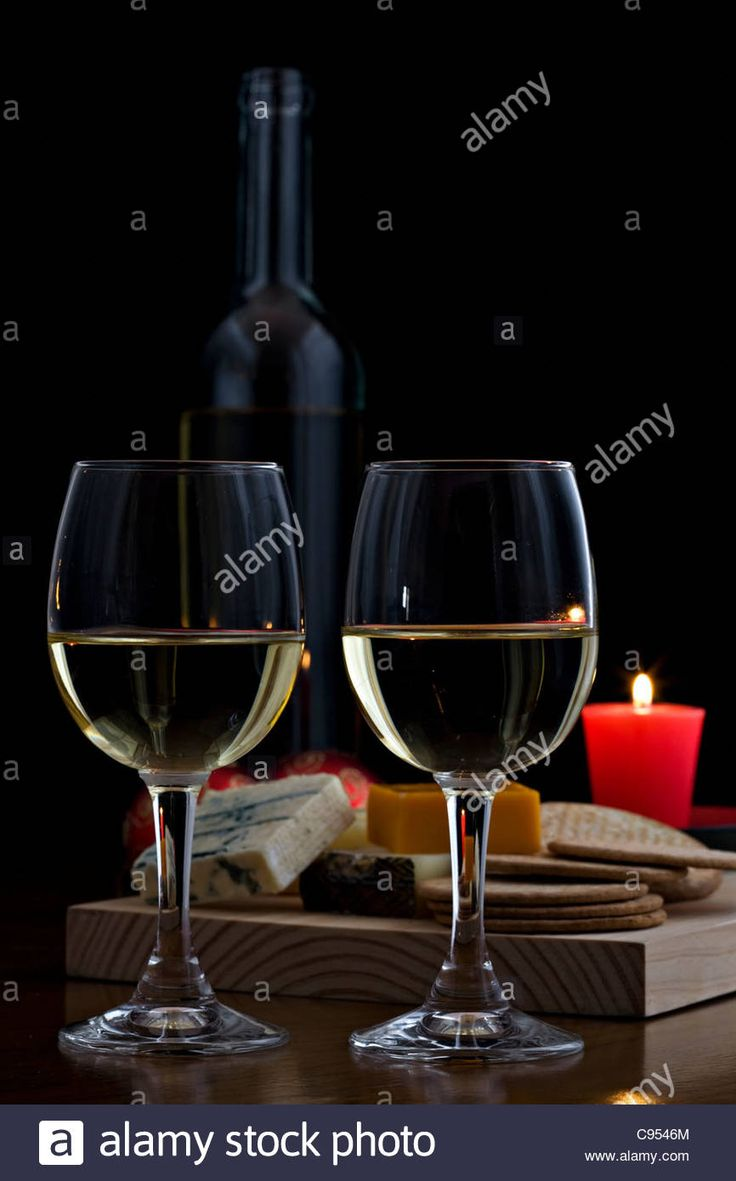 Two glasses of white wine with cheese selection and biscuits on wooden board with red candle on dark background Stock Photo