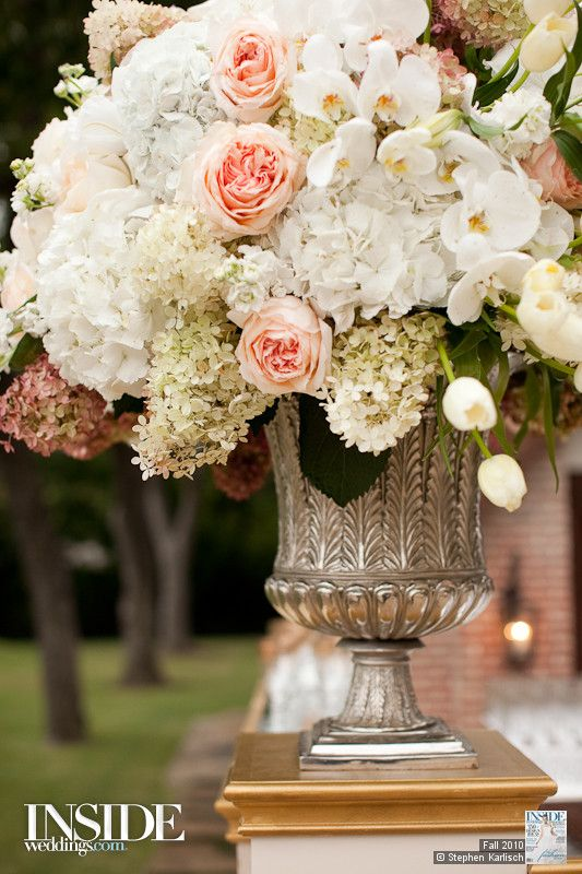 Two lucite risers topped with gold urn vases overflowing with large sprays of white phalaenopsis orchids, white hydrangeas, ivory garden roses and white spray roses will frame the altar.