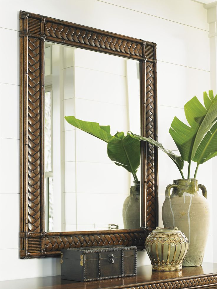 The perfect accent piece to accompany your display of found seashells and sea stars, this captivating tropical mirror boasts a decorative braid motif with a rattan border and leather wrapped pencil rattan corners. Use the mirror vertically or horizontally, as a wall mirror or accompanying a dresser, sofa table, or buffet for a complete look.