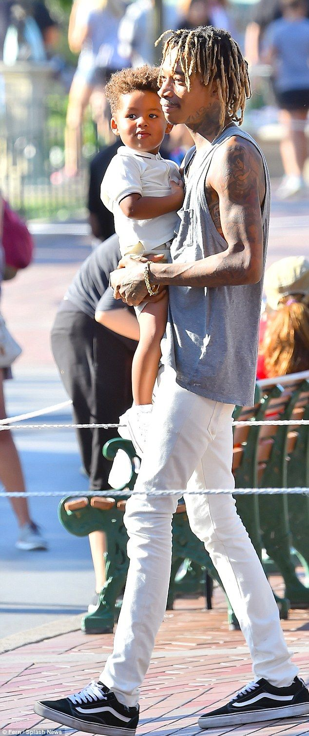 Father-son time! Wiz Khalifa was all smiles while carrying around his beaming little boy Sebastian during their sunny outing to Disneyland in Anaheim on Monday