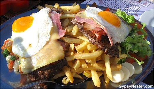 Chivito Gigante! Two huge hunks of cow, slices of ham, slabs of bacon ...