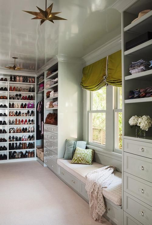 Chic walk-in closet boasts a a light gray built-in window seat with drawers placed under two windows dressed in chartreuse roman shades flanked by built-in ...
