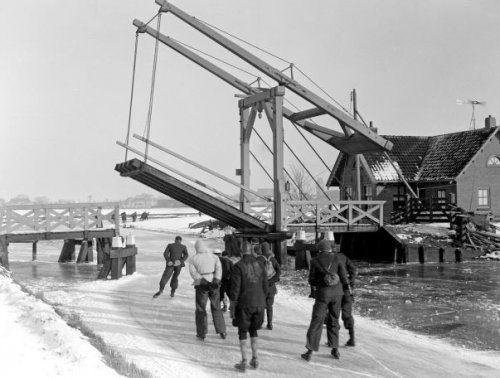 Schaatsen. Deelnemers aan de Elfstedentocht passeren schilderachtige Friese brug.