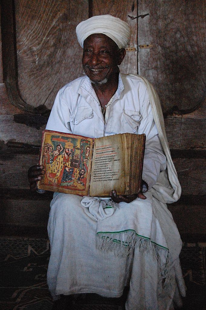 Coptic priest holding a 900 year old Coptic Bible, Ethiopia.