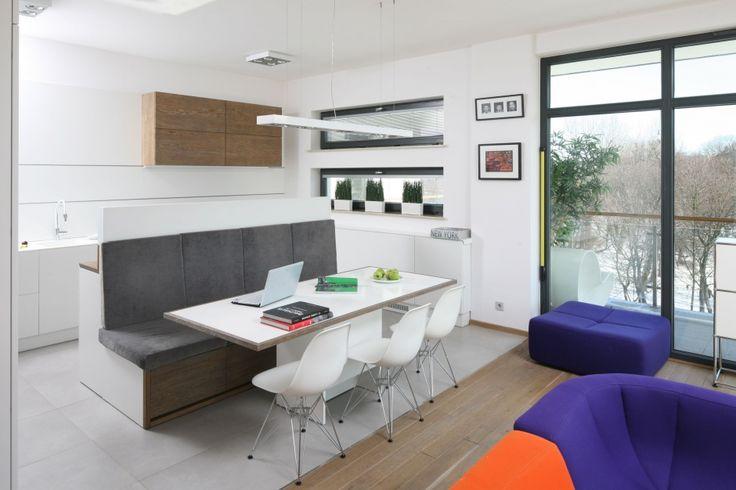 Skąpana w bieli kuchnia płynnie łączy się z multikolorowym salonem. Granicę między nim wyznacza praktyczna wyspa, która od strony salonu stanowi oryginalne siedzisko. Przy nim ustawiono stół jadalniany z designerskimi krzesłami. Projekt Konrad Grodziński. Fot. Bartosz Jarosz.
