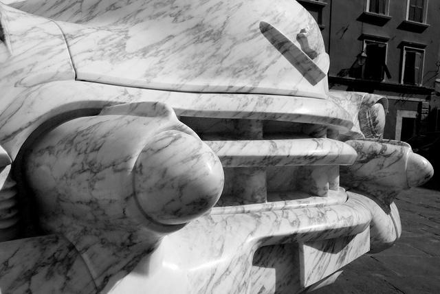 Cadillac modello 1952 in marmo, esposta per la prima volta a  Carrara Marble Week è uno degli esempi più interessanti di Pop Art, un pezzo da amatore (facoltoso) scolpita con un anno di intenso lavoro nel 1986 nello studio di Silvio Santini, Paolo Grassi e Mario Fruendi, tre amici, artigiani-artisti tutti formati dall'Istituto Professionale del Marmo in Carrara, che lavorano assieme dal 1972 nello studio che porta le loro iniziali.
