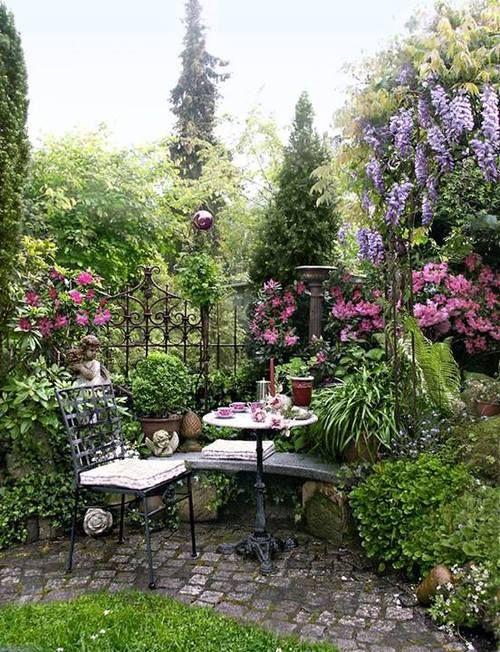 Pretty outdoor eating area on a brick paver patio surround by flowers
