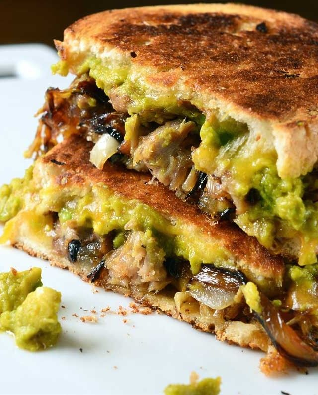 A delectable grilled cheese sandwich with pulled pork, caramelized onions and spicy sriracha guacamole.